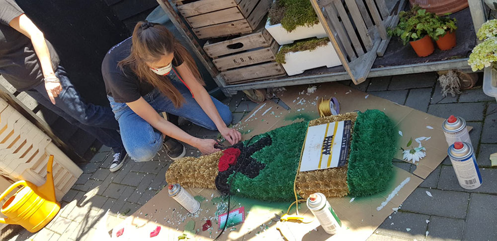 Florist making a funeral tribute shaped like a champagne bottle