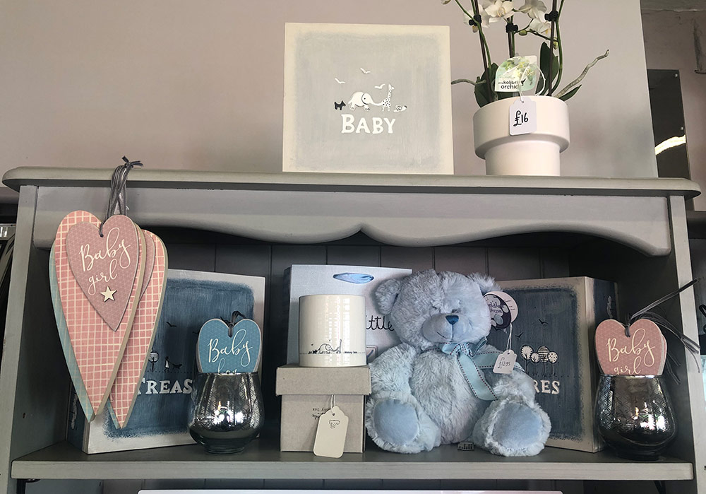 Shelf displaying new baby gifts such as a blue teddy bear, wooden memory boxes and porcelain money box