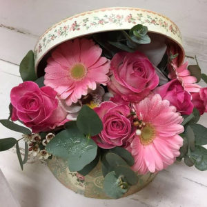 A pretty mixture of pink flowers arranged in a hat box