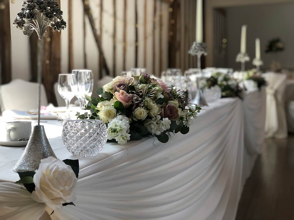 Flower arrangement on the top table at a wedding